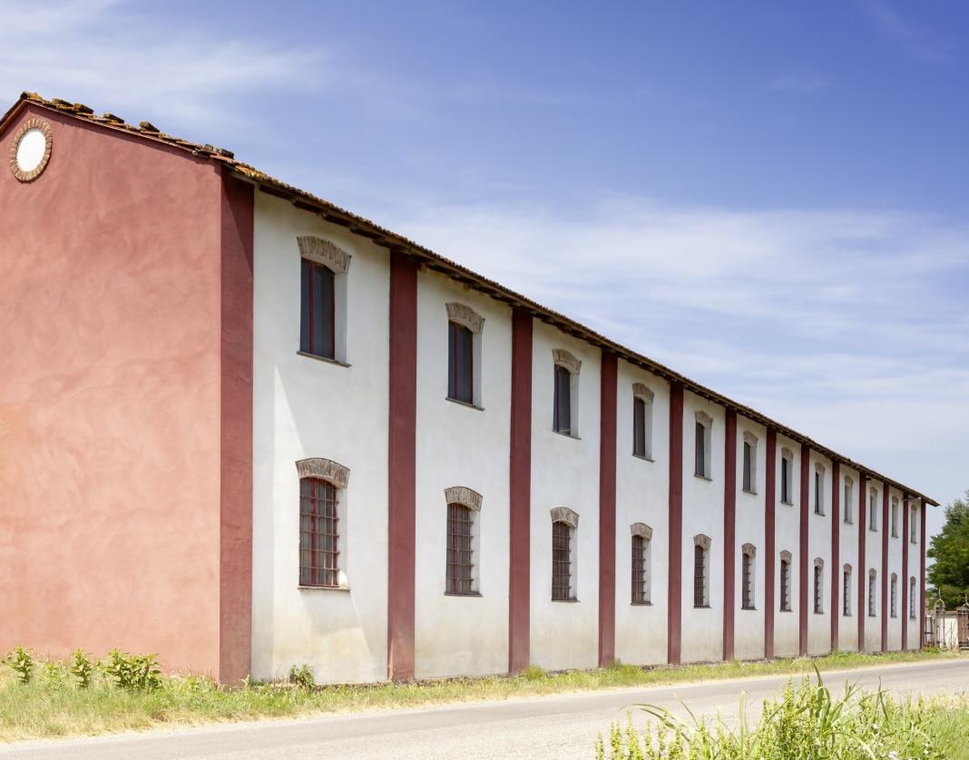 Grande edificio per la lavorazione del riso a Mede, su due piani, di colore bianco e rosa antico.