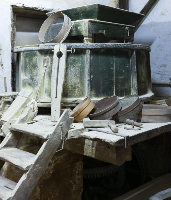 Storica macchina il legno per la lavorazione del riso integrale biologico, situata su un supporto con una scaletta di legno a 4 gradini. Alla base alcuni setacci.