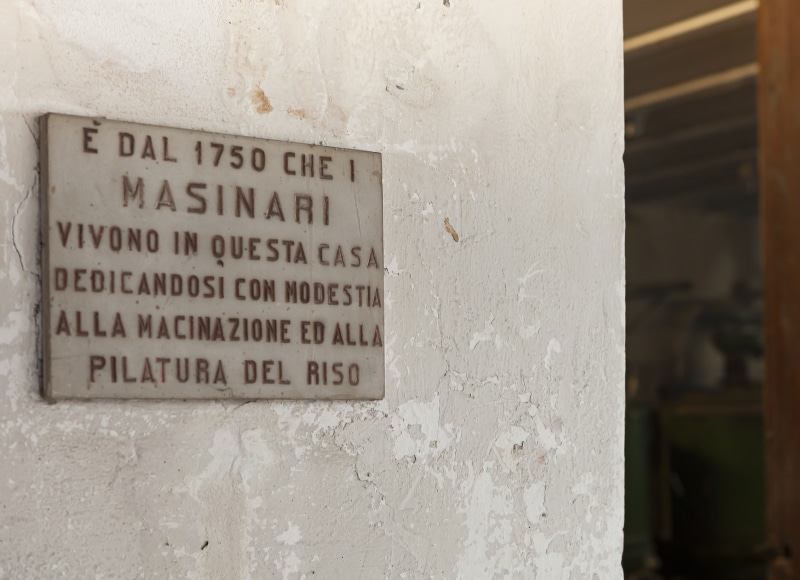 """Targa commemorativa all'ingresso della riseria Masinari riportante il testo """"E' dal 1750 che i Masinari vivono in questa casa dedicandosi con modestia alla macinazione ed alla pilatura del riso""""."""