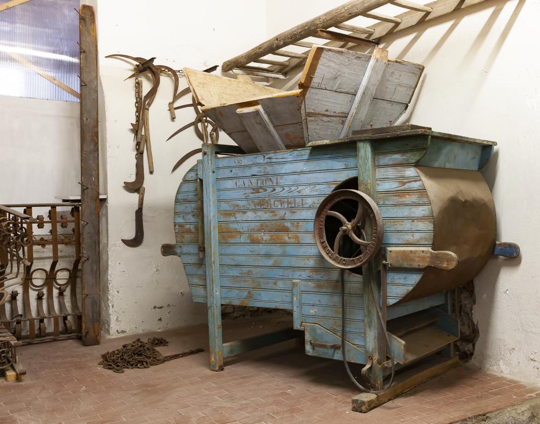 Antica macchina per la lavorazione del riso a Mede, in legno dipinto di azzurro con un grande imbuto nella parte superiore e un volano in metallo scuro sulla parete laterale.