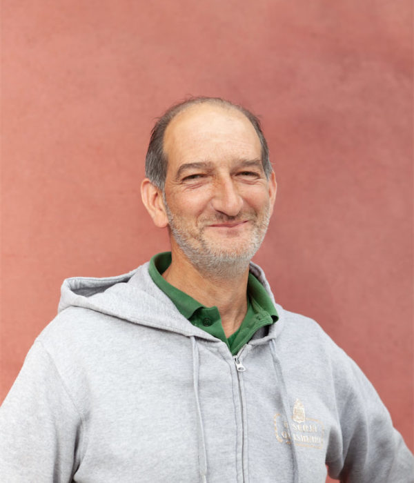 Mezzo busto su sfondo color salmone di un uomo sorridente con capelli e barba leggera brizzolati. Il soggetto, sopra una polo verde, indossa una felpa grigia con il logo della Riseria Masinari, lo stabilimento dove si lavora il riso.